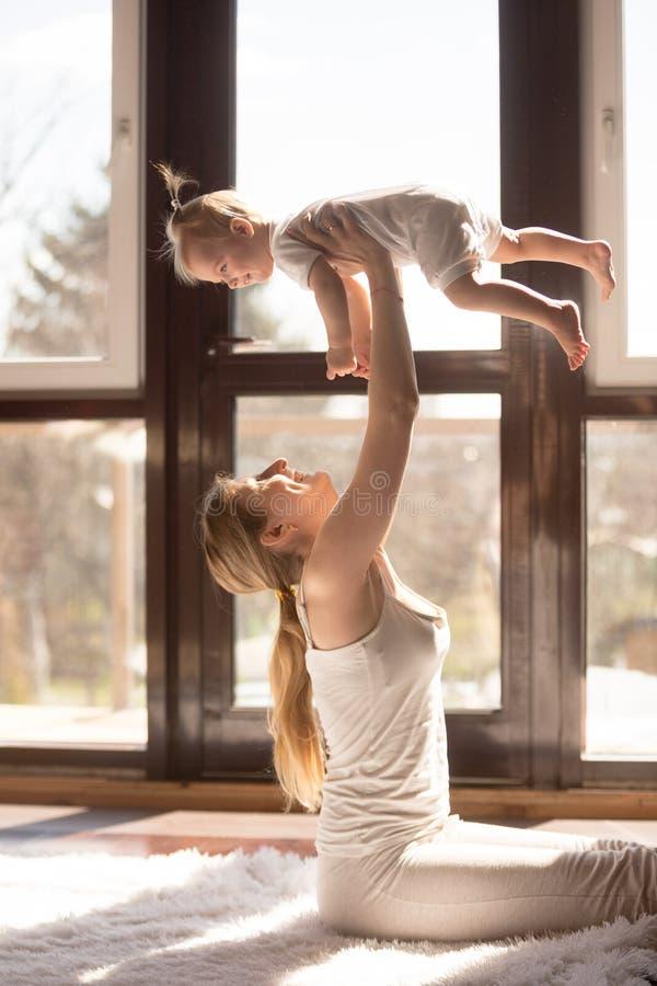 坐年轻人微笑的可爱的母亲拿着她的婴孩daughte 库存图片