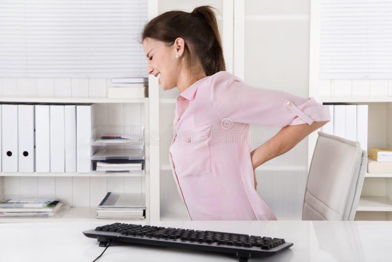 坐以腰疼的少妇在办公室 库存照片