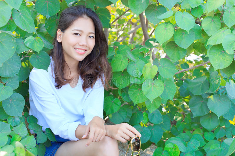 坐以绿色的俏丽的妇女画象离开灌木和smilin 库存照片