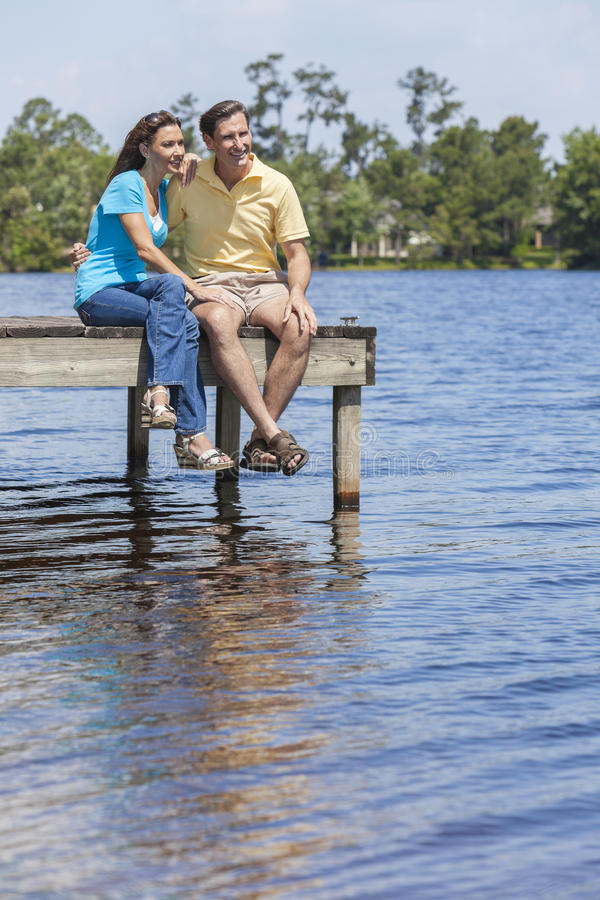 坐Lake的浪漫男人和妇女夫妇 免版税库存照片