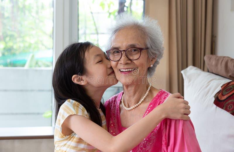 坐o的逗人喜爱的小女孩和她美丽的祖母画象  免版税库存图片