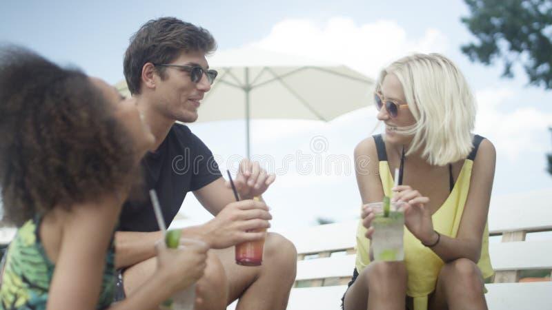 坐sunbeds在伞下和享受假期的年轻美丽的混合的族种朋友 免版税库存图片