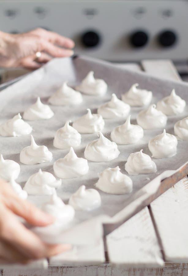 结块准备好的蛋白甜饼进来在烤箱 图库摄影