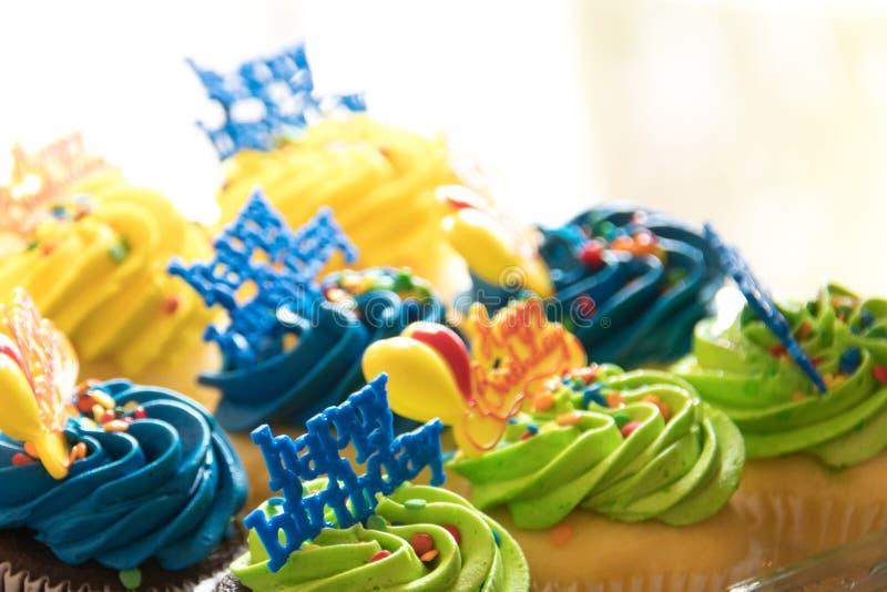 8块多彩多姿的生日快乐杯形蛋糕为装边与淡色五彩纸屑洒 免版税库存图片
