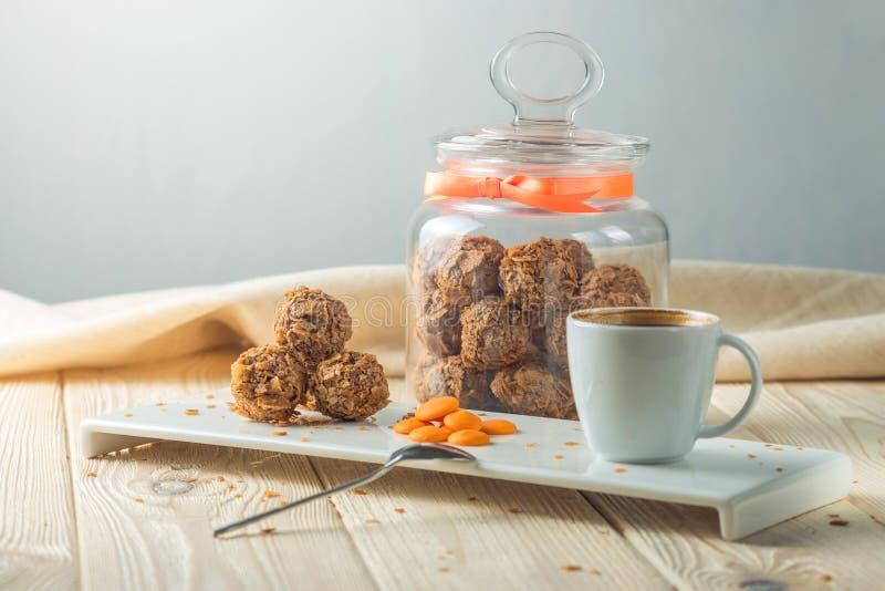 块菌球用在茶碟的橙色巧克力在瓶子糖果和一杯咖啡旁边 库存图片