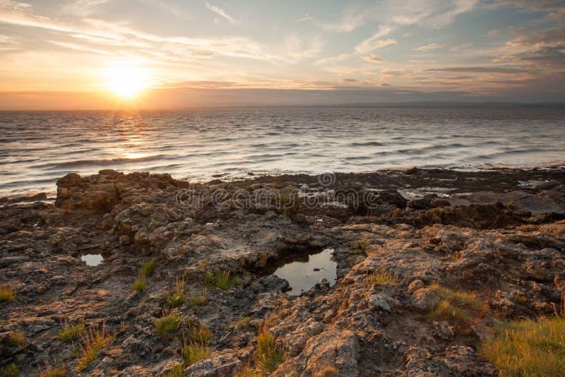 坚固性日落海岸线由晚上光束打开了 免版税库存图片
