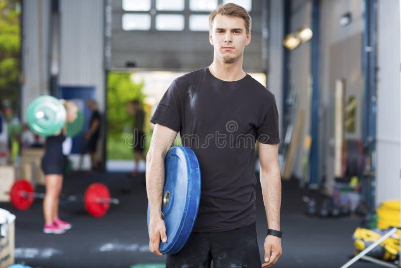 坚定的在健身俱乐部的运动员运载的重量板材 库存图片