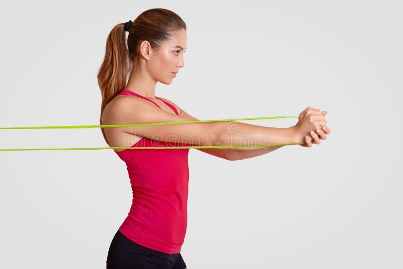 坚定的女运动员斜向一边的射击做舒展与健身胶的锻炼,在肌肉工作,穿戴在偶然T恤杉, h 免版税库存照片