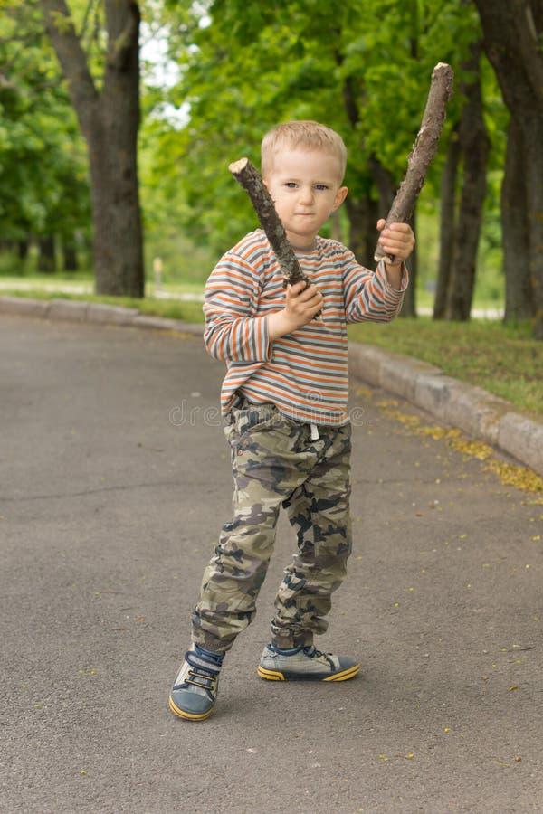 坚定的强壮男子的小男孩棍子战斗 免版税库存图片