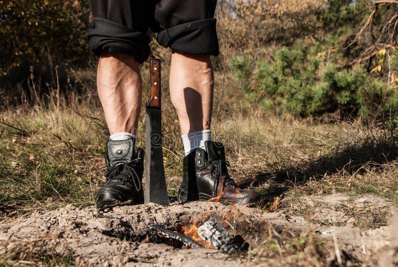 坚强男人的腿,站立在地面和大砍刀后困住的burnig火 免版税库存照片