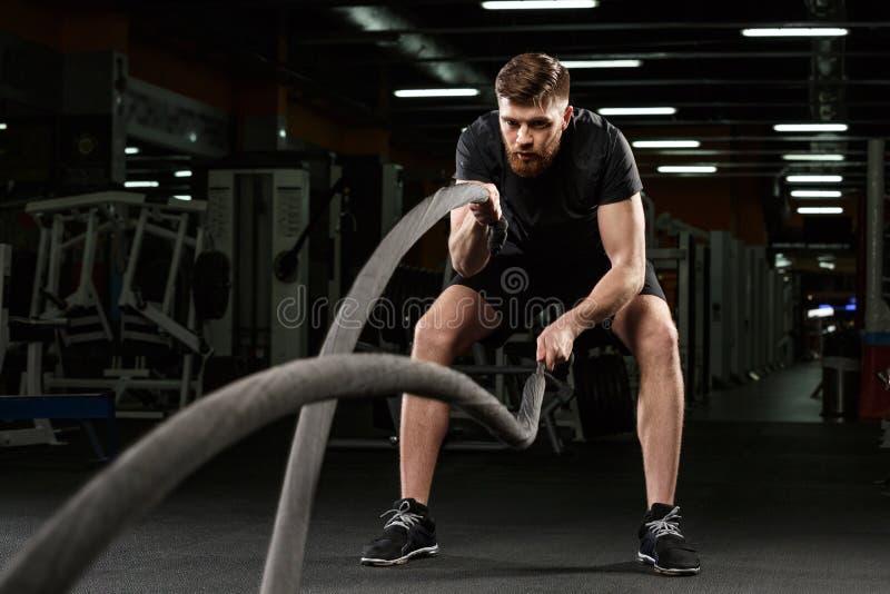 年轻坚强的体育人做在健身房的体育锻炼 免版税图库摄影
