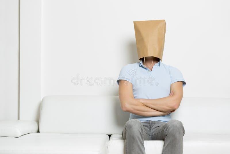 坚强的匿名人坐有横渡的胳膊的沙发。 免版税库存照片