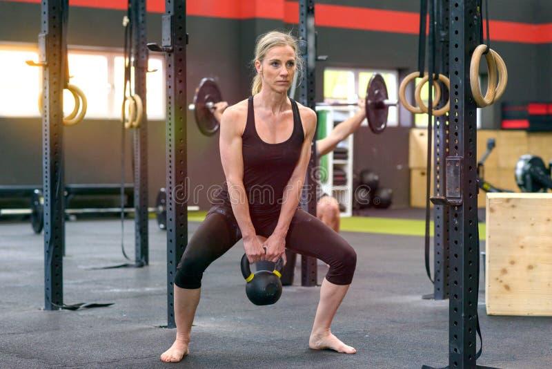 坚强的在健身房的适合妇女举的杠铃重量 库存照片