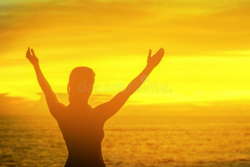 坚强的在日出下的信心妇女开放胳膊在海边 免版税库存照片