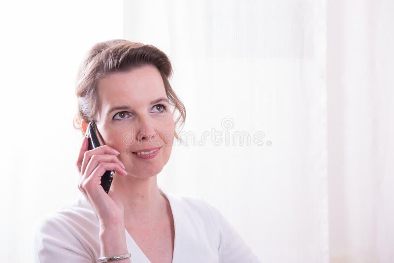 坚强的妇女在电话谈话 图库摄影