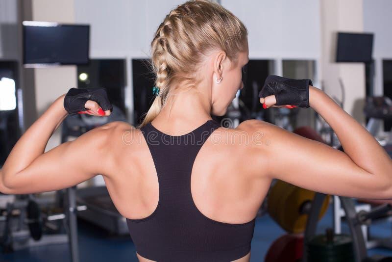 坚强的妇女显示她肌肉 免版税图库摄影