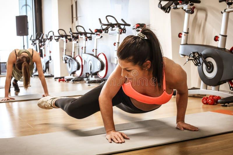 坚强的妇女 炫耀妇女在健身房 免版税库存图片