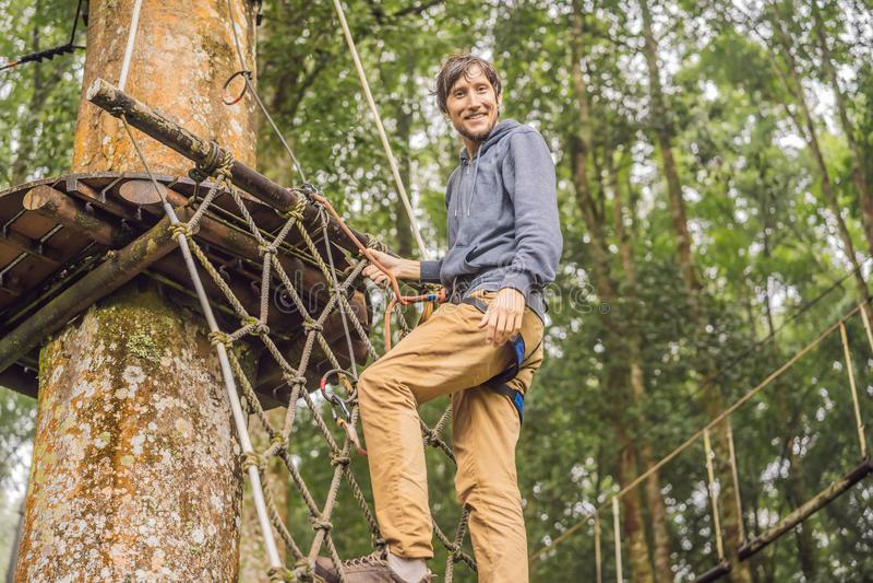 坚强的年轻人在木背景的一个绳索公园 库存图片