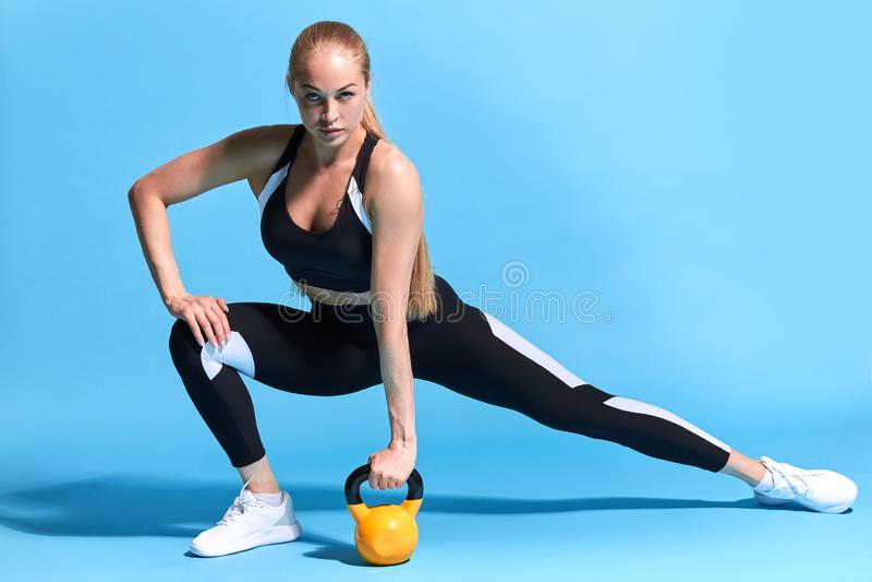 坚强的有动机的美女运作的outwith kettlebell 图库摄影