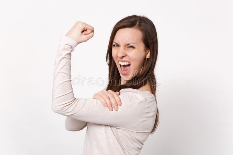 坚强的疯狂的叫喊的年轻女人画象显示二头肌,肌肉的轻的衣裳的隔绝在白色墙壁上 免版税图库摄影