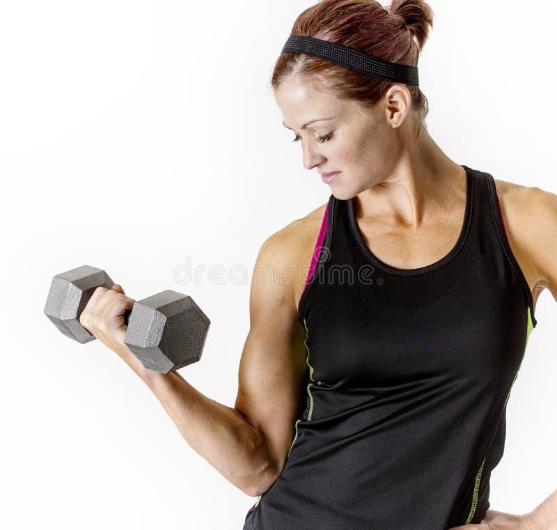 坚强的美丽的健身妇女举的哑铃重量 库存照片