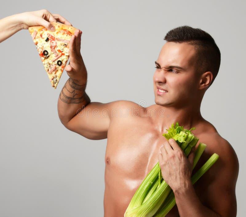 坚强的肌肉运动员人用新鲜的芹菜和不健康的薄饼快餐 库存照片