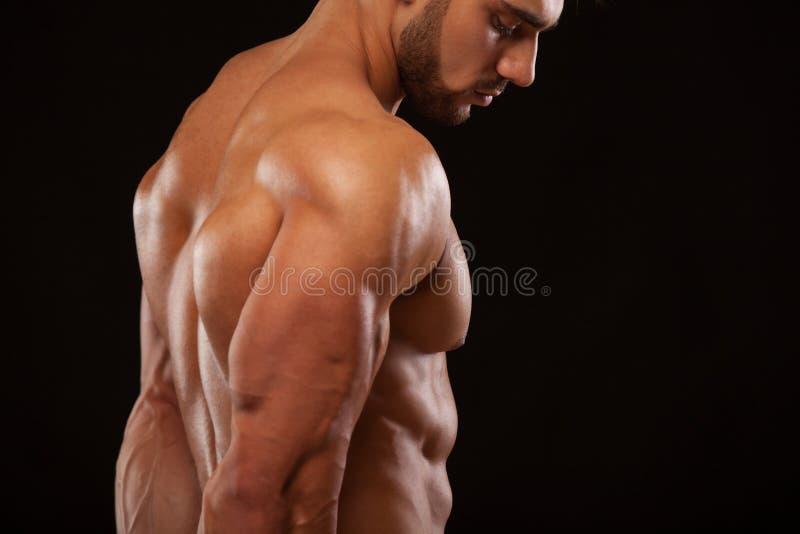 坚强的运动人-显示他完善的后面的健身模型隔绝在与copyspace的黑背景 免版税库存图片