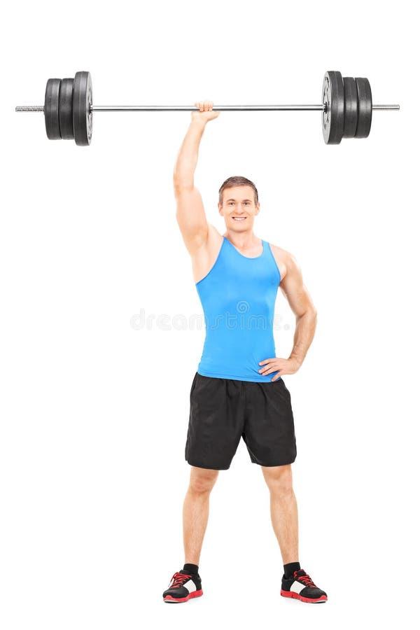 坚强的运动员在一只手上的拿着重量 免版税图库摄影
