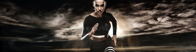 坚强的运动妇女短跑选手,跑在佩带在运动服的黑暗的背景 健身和体育刺激 赛跑者 免版税图库摄影