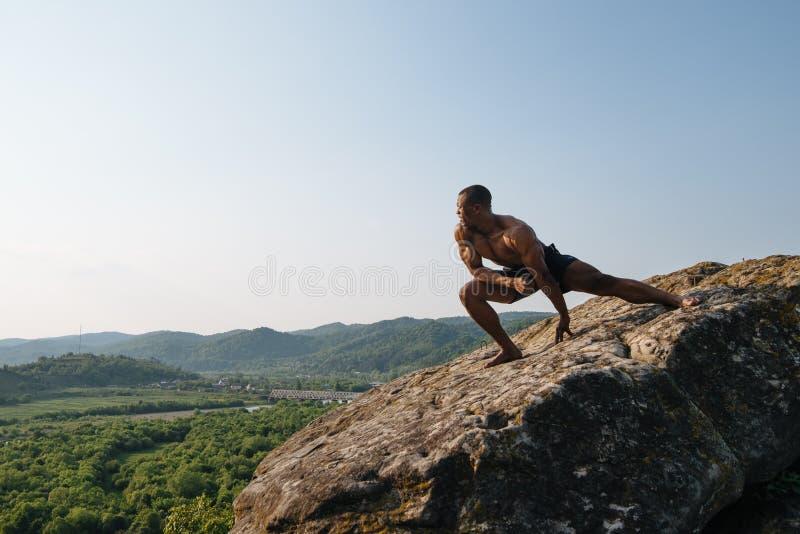 Download 坚强的非裔美国人的爱好健美者在山的岩石训练 绿色森林山背景 库存图片 - 图片 包括有 顿断法, 设计: 72367085