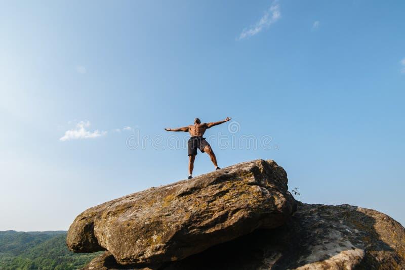 Download 坚强的黑人爱好健美者画象有摆在岩石的赤裸躯干的 蓝色多云天空背景 库存图片 - 图片 包括有 佩奇, 运动: 72365987