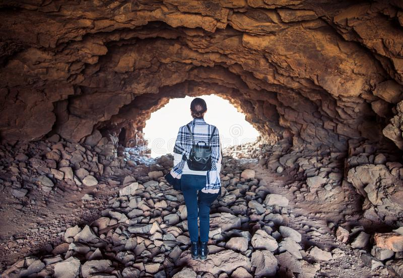 坚持在洞的妇女被点燃的出口 免版税图库摄影