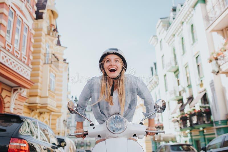 坚持女孩尝试对摩托车起动工作 她恼怒 她能` t乘驾 女孩头戴盔甲 她是在 免版税库存照片