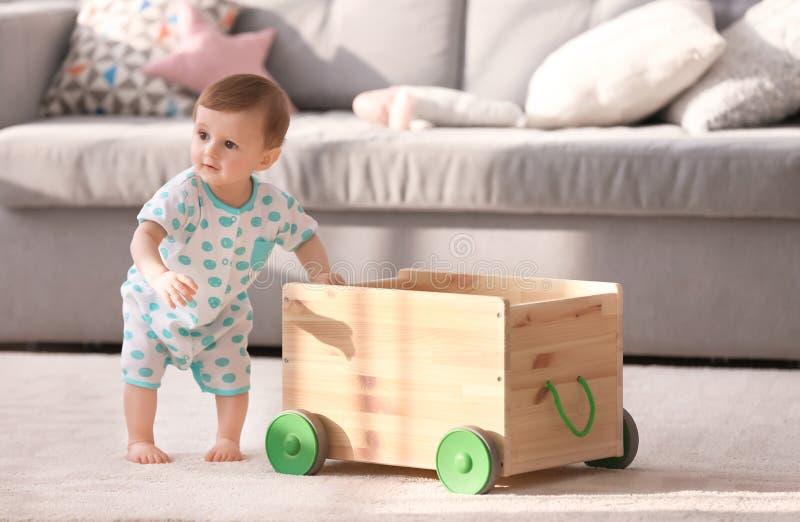 坚持木推车的逗人喜爱的婴孩在客厅 库存图片
