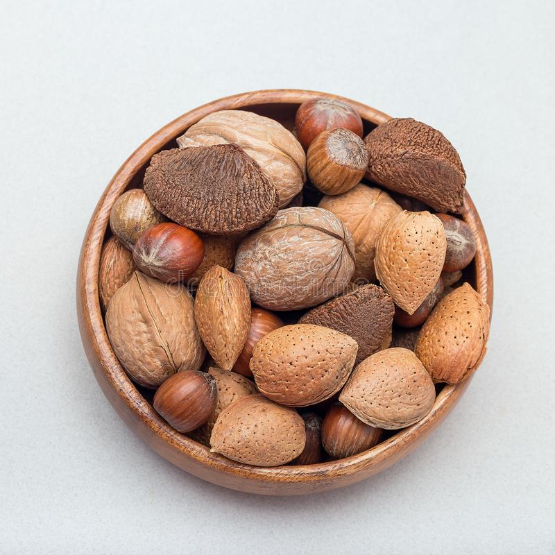 坚果不同形式在壳、榛子、核桃、杏仁和巴西坚果的在一个木碗,方形的格式,顶视图 库存图片