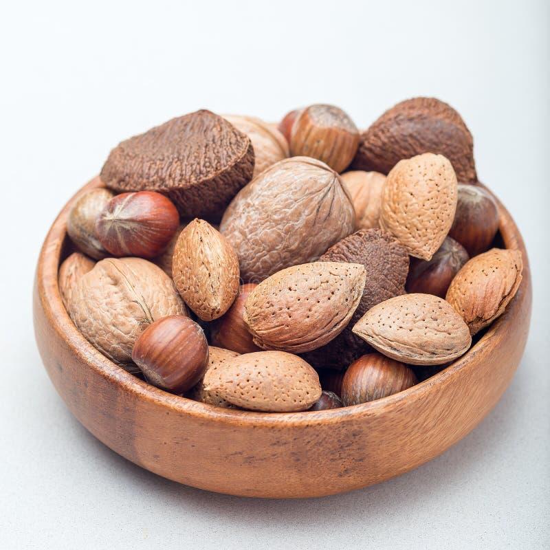 坚果不同形式在壳、榛子、核桃、杏仁和巴西坚果的在木碗,方形的格式 免版税库存照片