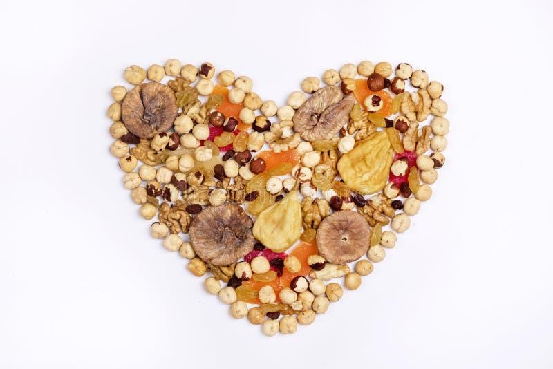 坚果混合和干果子在心脏形状在白色背景顶视图 图库摄影
