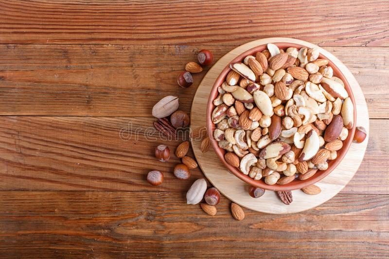 坚果混杂的不同形式在陶瓷碗的在与拷贝空间的棕色木背景 图库摄影