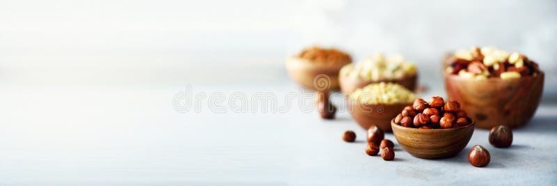 坚果的分类在木碗的 腰果,榛子,核桃,开心果,胡桃,松果,花生,葡萄干 食物混合 免版税库存图片