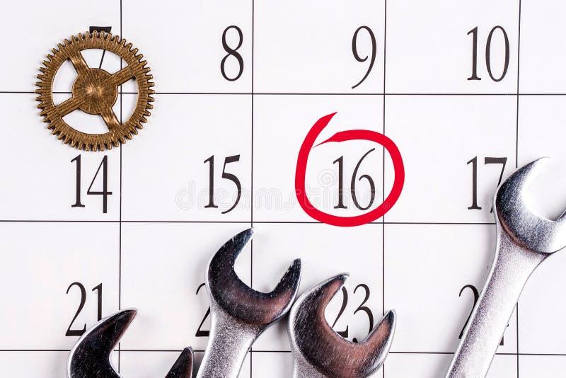 坚果的板钳和齿轮在日期是盘旋的16数字的日历 库存图片