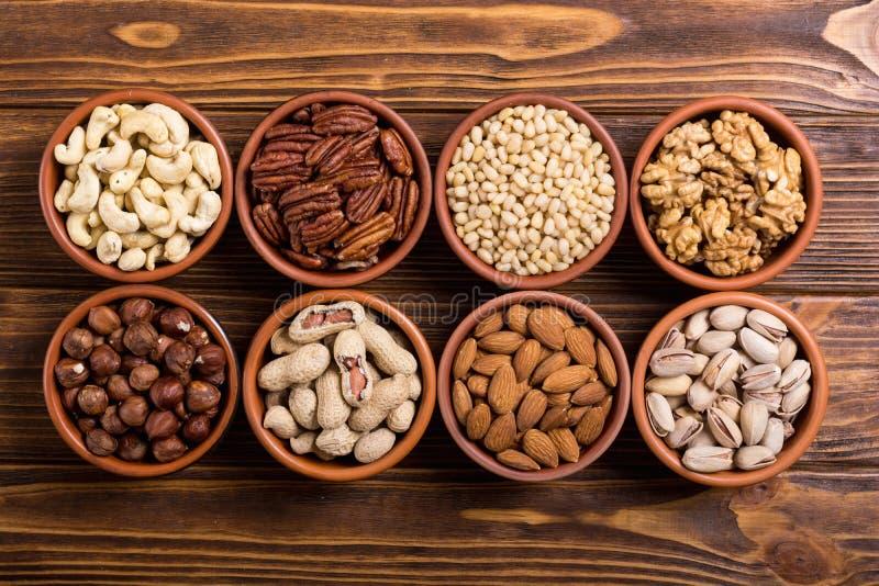 坚果的混合:开心果、杏仁核桃、松果、榛子和腰果 在碗backgrond的快餐 免版税库存照片