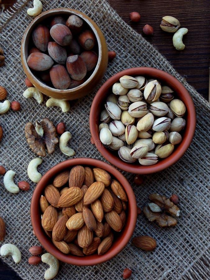 从坚果-杏仁,腰果,花生,核桃,榛子,开心果不同的品种的构成在木背景的 免版税图库摄影