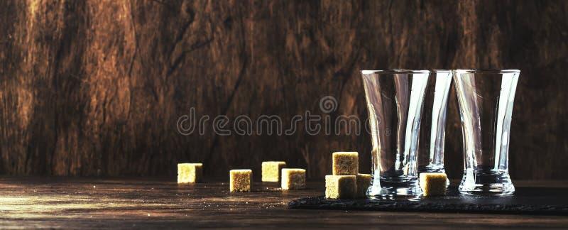 坚硬烈性饮料的空的小玻璃在木桌背景,选择聚焦 免版税库存图片
