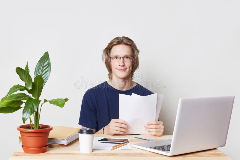 坚苦工作专业企业工作者在工作地点坐,回顾他的帐户,学习文件,看直接地入照相机 免版税库存图片