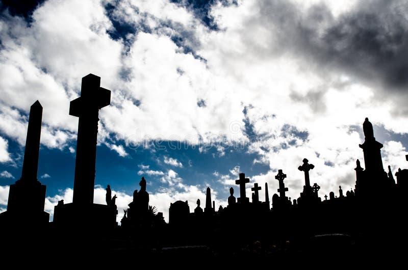 坟园剪影,图象显示许多与剧烈的多云天空的发怒墓碑 库存照片