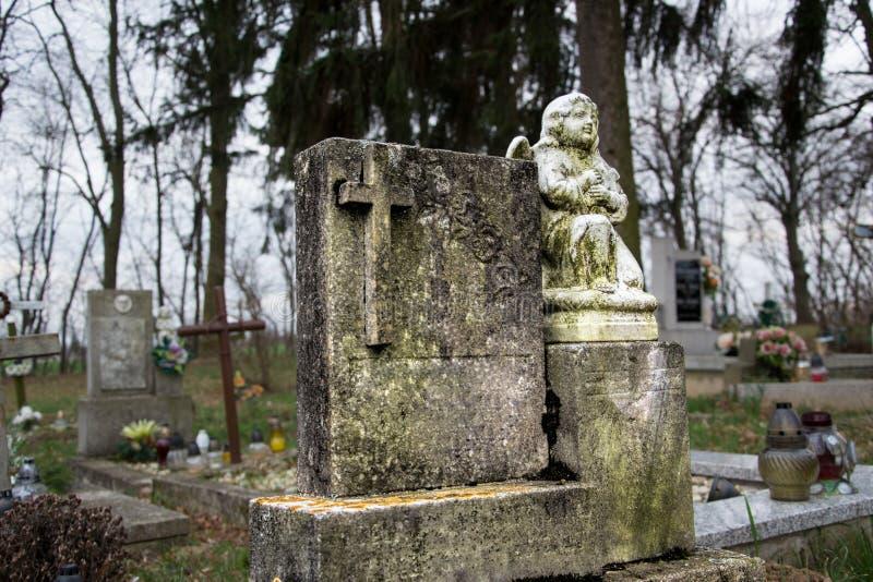坟墓、墓碑和耶稣受难象在传统公墓 一个天使的雕象在老坟茔石头的在坟园 所有Saints& x27;天 免版税库存图片