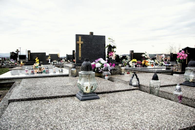 坟墓、墓碑和耶稣受难象在传统公墓 奉献的蜡烛灯笼和花在坟茔石头在坟园 库存照片