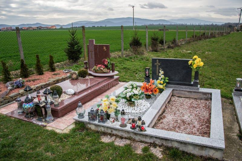 坟墓、墓碑和耶稣受难象在传统公墓 奉献的蜡烛灯笼和花在坟茔石头在坟园 图库摄影