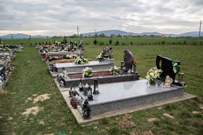 坟墓、墓碑和耶稣受难象在传统公墓 奉献的蜡烛灯笼和花在坟茔石头在坟园 免版税库存图片