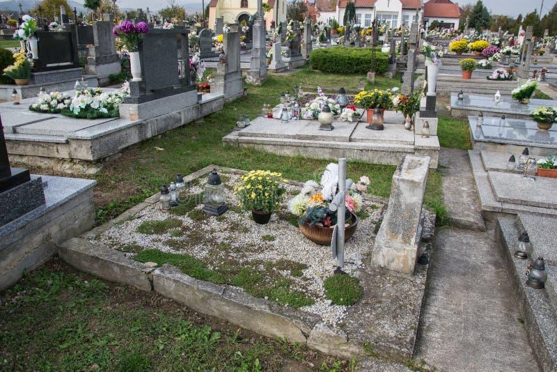 坟墓、墓碑和耶稣受难象在传统公墓 奉献的蜡烛灯笼和花在坟茔石头在坟园 库存图片